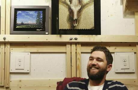 San Antonio artist Matt Tumlinson poses with his works in his studio space at Hausmann Millworks. Tumlinson works with bullet casings as a canvas for art, a medium he calls Bullet Canvas, by using casings he collects at his uncle's shooting range.
