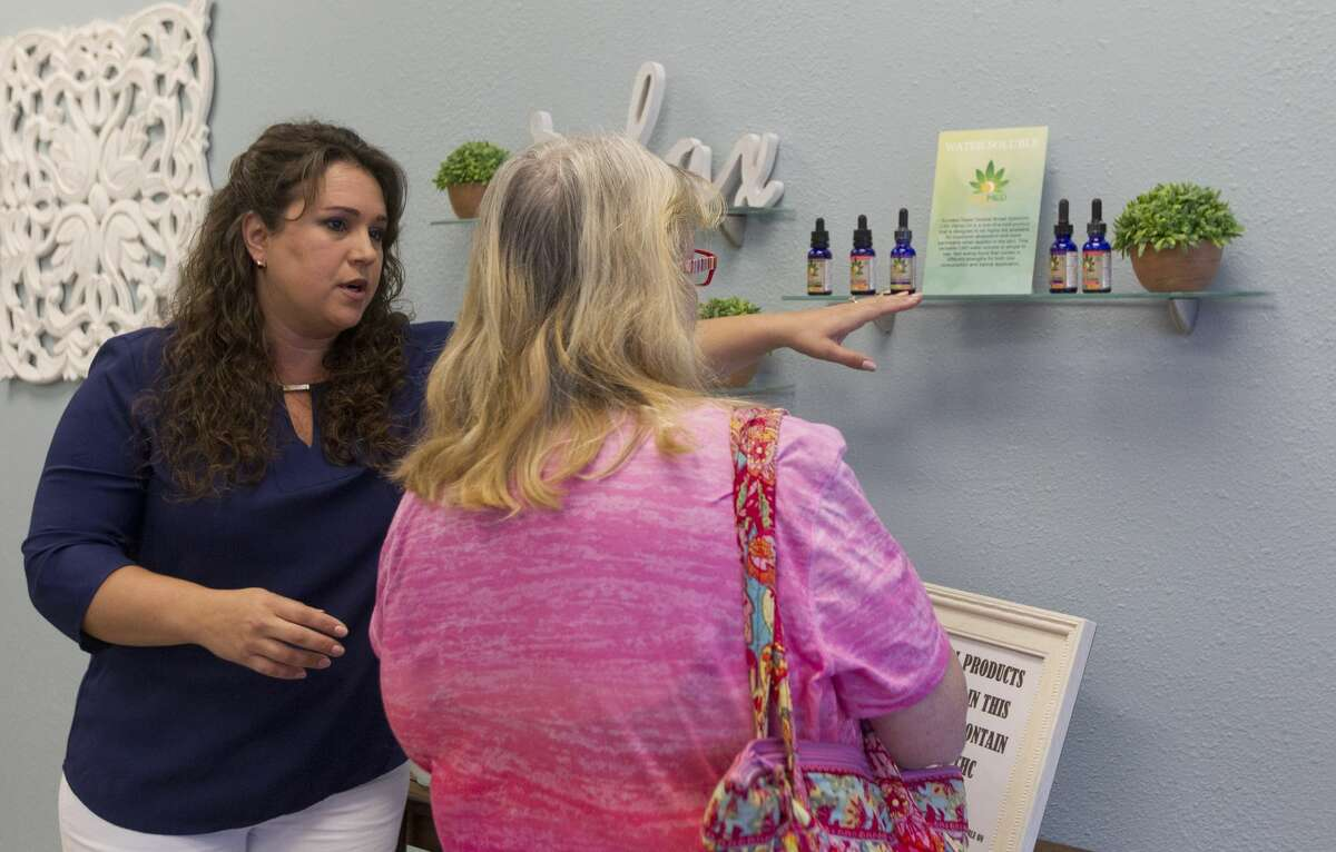 Jennifer Harris, co-owner of Your CBD Store, works with a customer, Thursday, March 7, 2019, in Willis.