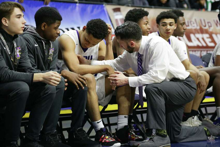 Troy's Nazaire Merritt, is consoled after Friday's Class A semi-final loss to Mendon at the boy's basketball state championships in Binghamton.