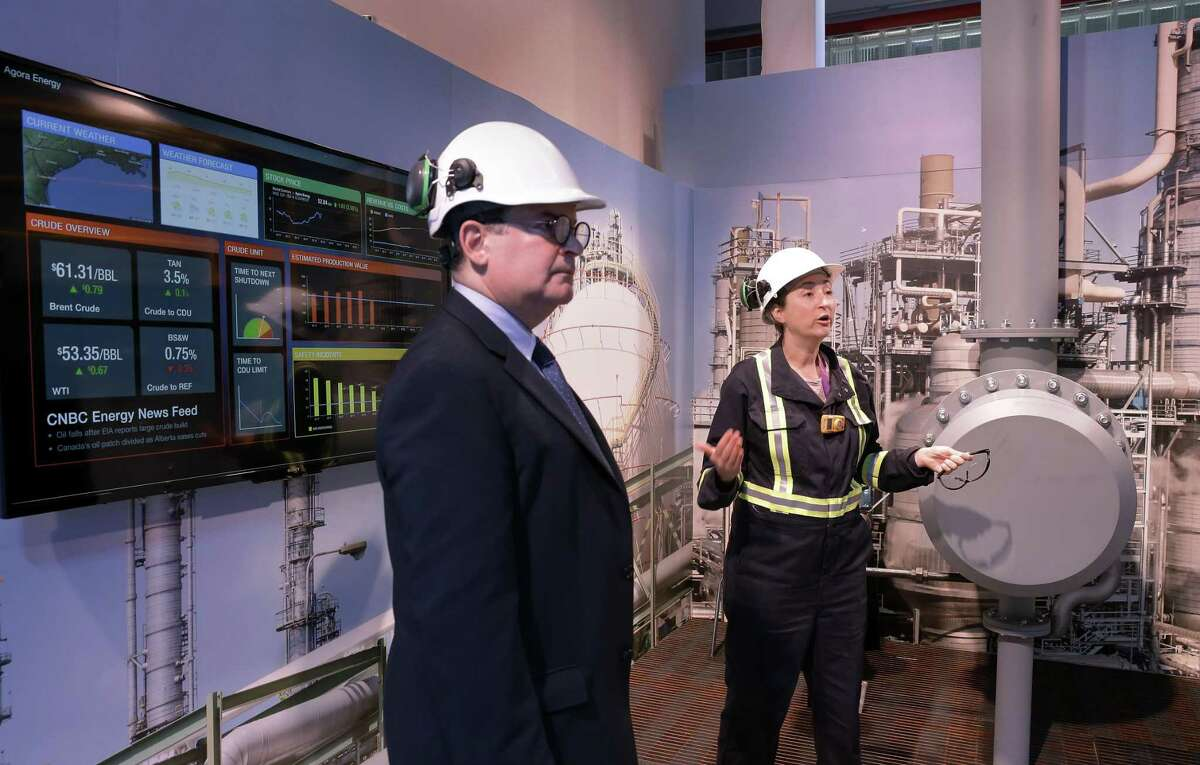 Two actors, Jim Cunningham (l) and Mo Perry (r), demonstrate Emerson's automation technology to visitors at a pipeline mock-up during CERAWeek by IHS Markit. Emerson helps customers implement industrial internet of things technology and works with Microsoft Azure to link equipment to cloud among other services.