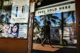 FILE-- A tobacco and e-cigarette shop in Miami Beach, Fla., Dec.  18, 2018. Juul and Big Tobacco have lobbied for months to protect themselves from aspects of the FDA's crackdown. As Gottlieb leaves in 2019, they see an opening. (Scott McIntyre/The New York Times)