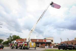 A Conroe fire engine lifts a US flag over downtown Conroe during the Fire Up the Bands concert, benefiting the Conroe Professional Firefighters Association, on Saturday, July 14, 2018, at Pacific Yard House.
