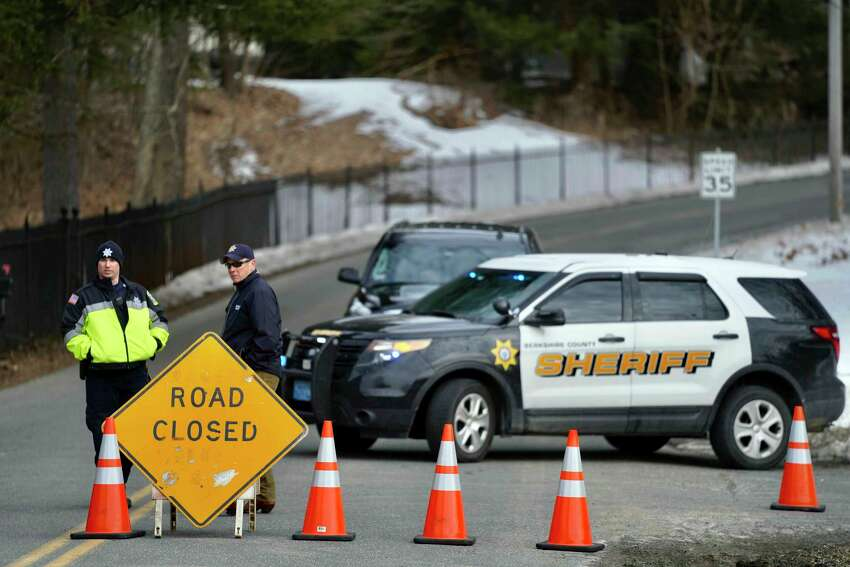 Berkshire County Sheriff Department officers close off the road Wednesday, March 13, 2019, in Sheffield, Mass., to a home where investigators work at the scene of a house fire that killed five people.