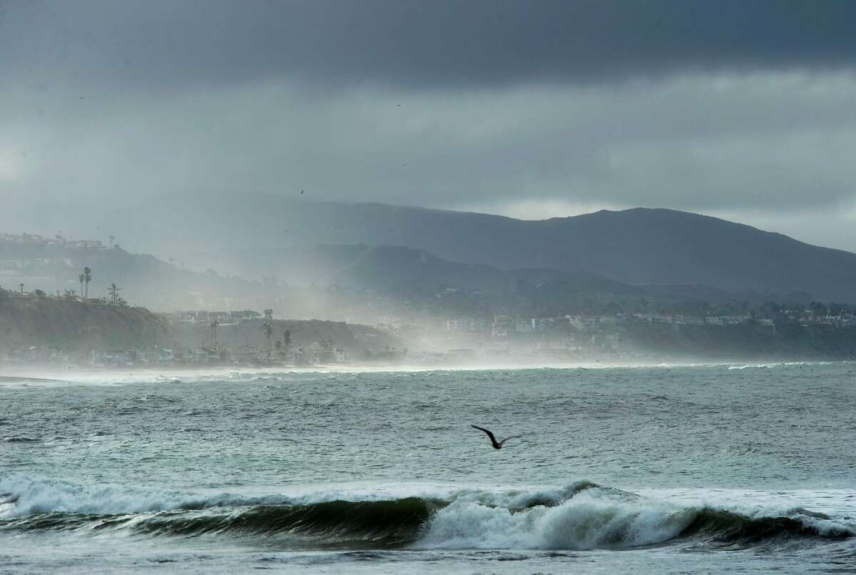 As a gull surveys the waves, the sun peeks out from the thick clouds of a passing storm front as it moves through Doheny State Beach in Dana Point lighting up the coastline at Capistrano Beach in spots, Wednesday, April 11, 2012. (AP Photo/The Orange County Register, Ken Steinhardt)