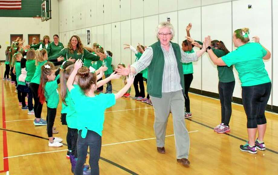 Kathy Dickens runs through a greeting line formed by students at an elementary pep assembly during the 2018 Coming Home Week. Dickens, currently the elementary principal at Elkton-Pigeon-Bay Port, will be leaving the district at the end of the school year for the position of executive director at the Four Corners Community Foundation in Almont. (Courtesy Photo)