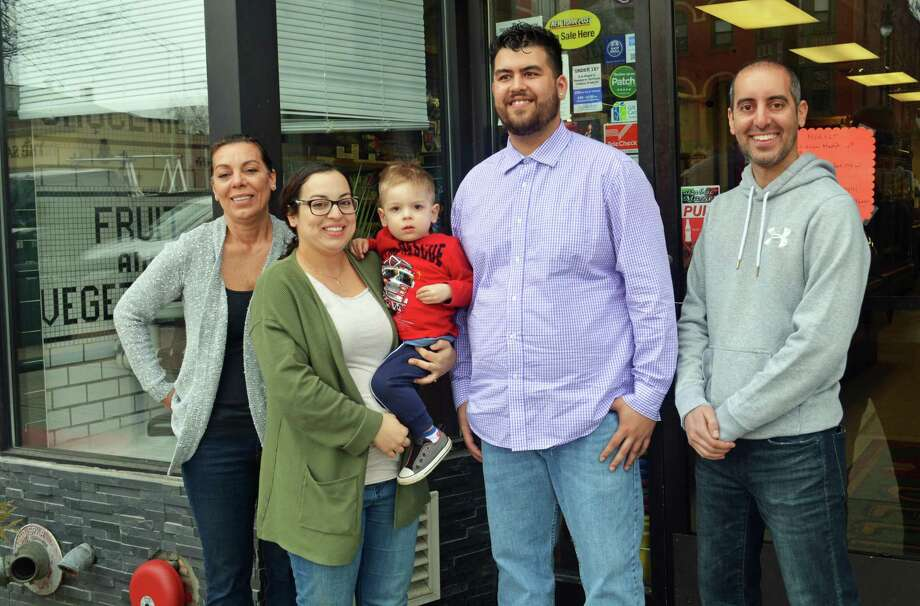 Josh Morris, second from right, is the new owner of Public Market, which has been at 480 Main St., Middletown, since 1915. Shown, from left are Maria Passacantando, Amelia Passacantando, Giovanni Passacantando, Morris and Middletown Police Officer John Passacantando. Morris purchased the shop Friday and will reopen its doors Monday morning. Photo: Cassandra Day / Hearst Connecticut Media