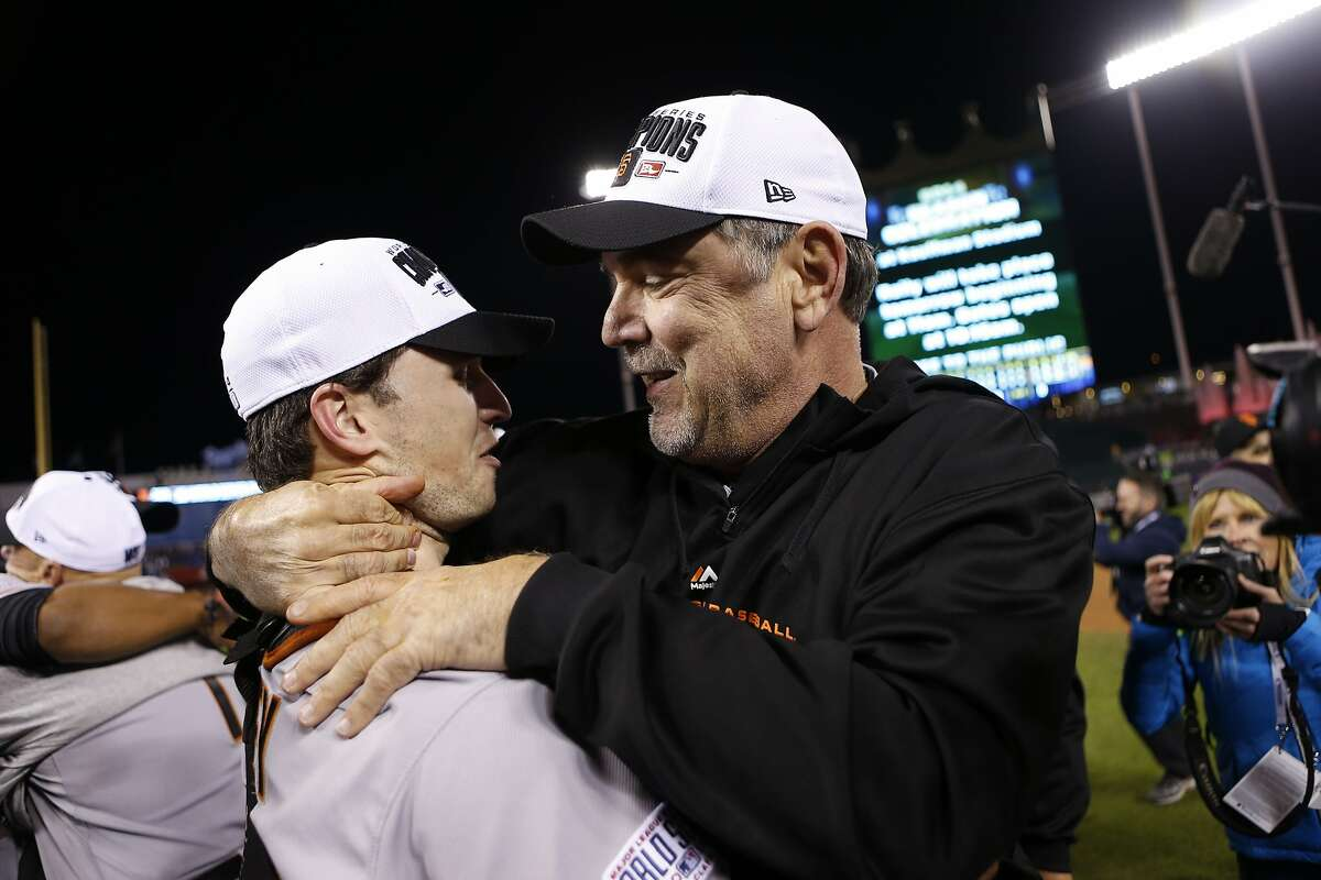 San Francisco Giants' manager Bruce Bochy and Buster Posey embrace after Game 7 of the World Series at Kauffman Stadium on Wednesday, Oct. 29, 2014 in Kansas City, Mo.