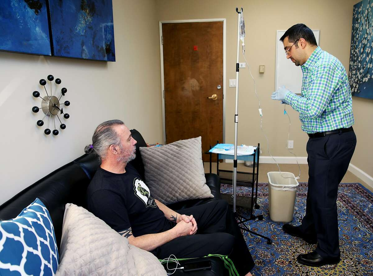 """Dr. M. Rameen """"Dr. G"""" Ghorieshi treats patient Joel W., 50, during a visit to Palo Alto Mind Body in Palo Alto, Calif., on Wednesday, March 13, 2019. Ghorieshi is preparing to give his patient a ketamine IV at the clinic. A new ketamine-based nasal spray treatment was approved by the FDA last week to treat severe depression. """"I think Dr. G offers a alternative to opioids and pysch medicines and stuff. And I think that the opportunity was presented to me and I took it and I'm real appreciative that Dr. G allowed me to come to his office and participate in the program,"""" said W, who served in the Navy for nearly seven years. """"I think that anybody that has PTS, whether it be through the military, through law enforcement, through traumatic incidents at home, through any traumatic incident, domestic abuse, whatever, I think people could benefit from this. It's an opportunity to take care of yourself so that you can take care of others."""""""