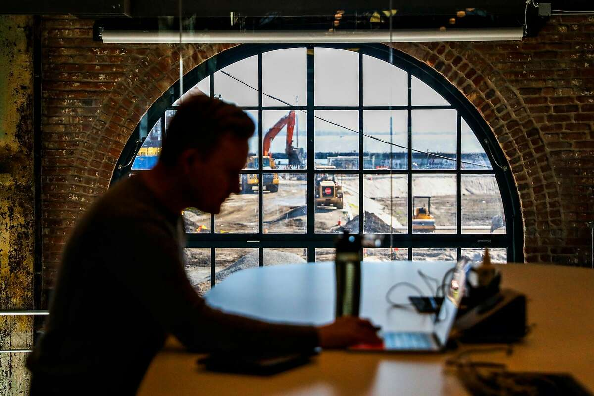 Michael Hutto works in the Gusto offices as construction can be seen outside the window on Wednesday March 13, 2019 at Pier 70 in San Francisco, California.