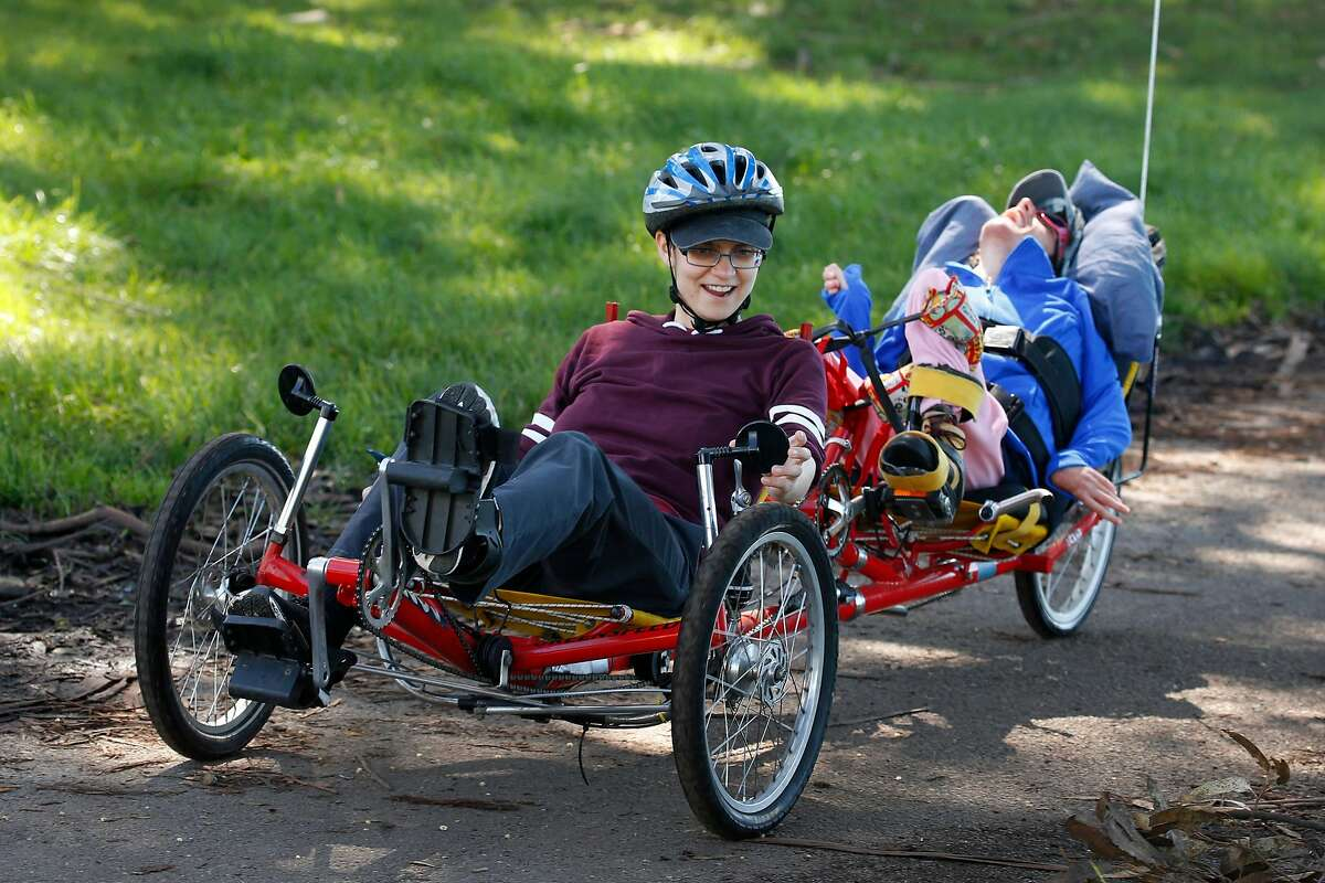 Ames Lefever (left) leads Jackie Donovan in an exercise program for persons with disabilities aboard a tandem recumbant bicycle provided by the BORP Adaptive Cycling Center at Aquatic Park in Berkeley, Calif. on Tuesday, March 12, 2019.