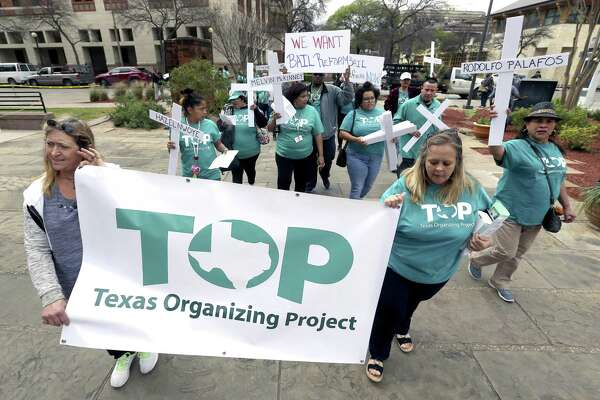 Members of the Texas Organizing Project march around the courthouse before presenting 20,000 signatures to Bexar judges backing the end of cash bail. Judges aren't receptive.