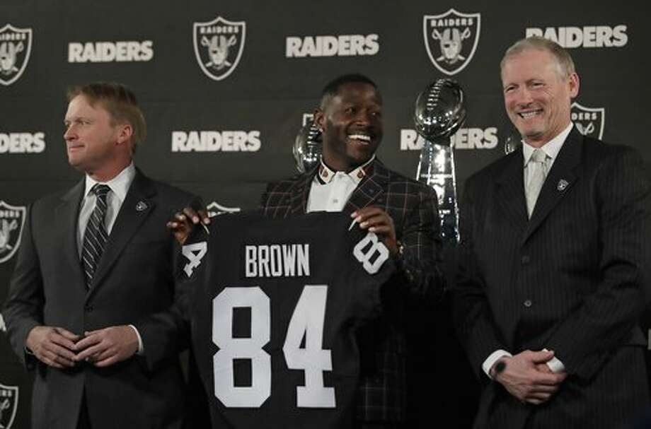 c7c34468be8 FILE – Oakland Raiders wide receiver Antonio Brown, center, holds his  jersey beside coach