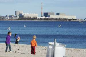 Families play on the beach with the Millstone Nuclear Power Plant in the background in Niantic, Conn. on Sunday March 20, 2011.