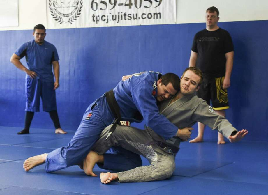 Instructor Jason Ebarb, in blue, shows how to preform a move with the help of Ian Kieth at TPC Brazilian Jiu-Jitsu & MMA on Friday. Photo taken on Friday, 03/15/19. Ryan Welch/The Enterprise Photo: Ryan Welch / The Enterprise / ©Ryan Welch