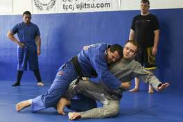 Instructor Jason Ebarb, in blue, shows how to preform a move with the help of Ian Kieth at TPC Brazilian Jiu-Jitsu & MMA on Friday. Photo taken on Friday, 03/15/19. Ryan Welch/The Enterprise