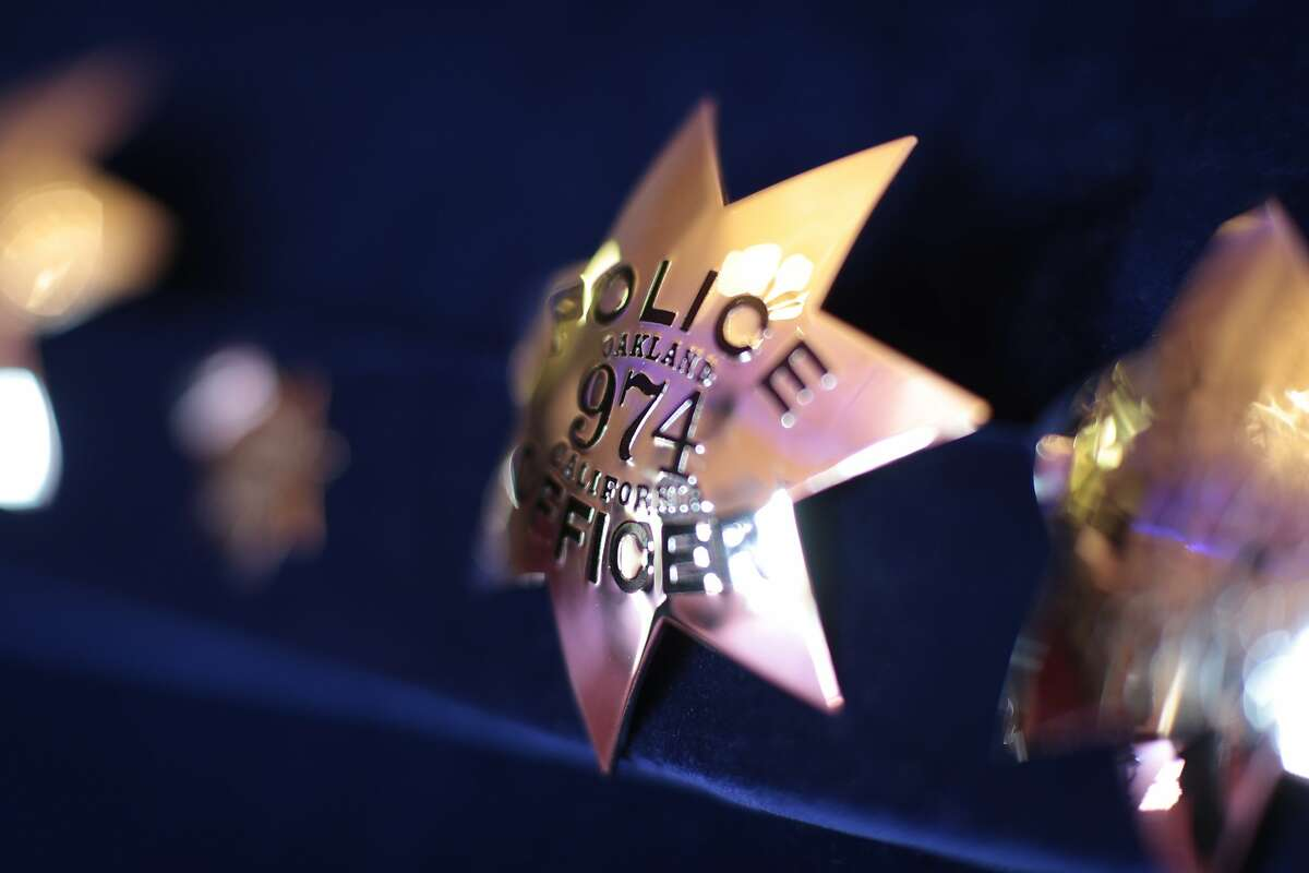 Police badges are on display before the graduation ceremony begins on Friday, Oct. 30, 2015 in Oakland, Calif. The 172nd police academy of Oakland celebrates graduation at the Scottish Rite Temple.