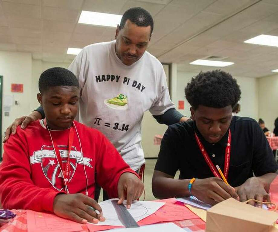 Working at the Pi in Measurements table are CHS freshmen Damien Johnson (left) and Sharrod Baldwin, as Greg Laktzian, CHS math teacher assistant, looks on. Photo: For The Intelligencer