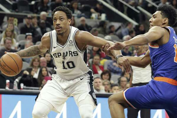 DeMar DeRozan gets held on a move to the rim by Allonzo Trier as the Spurs host the Knicks at the AT&T Center on March 15, 2019.