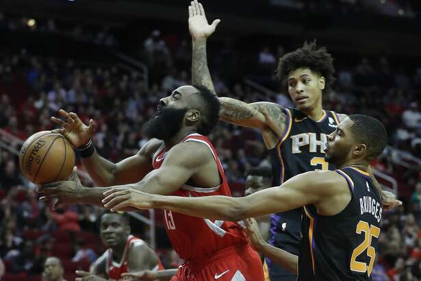 Houston Rockets guard James Harden (13) is fouled going to the basket by Phoenix Suns forwards Mikal Bridges (25) and Kelly Oubre Jr. (3) during the first half of an NBA game at Toyota Center, Friday, March 15, 2019, in Houston.