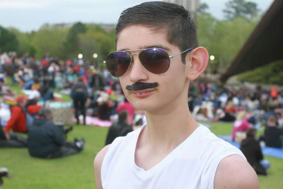 A fan attending One Night of Queen, at Miller Outdoor Theatre, a live concert recreating the look, sound, pomp, and showmanship of the band Queen.