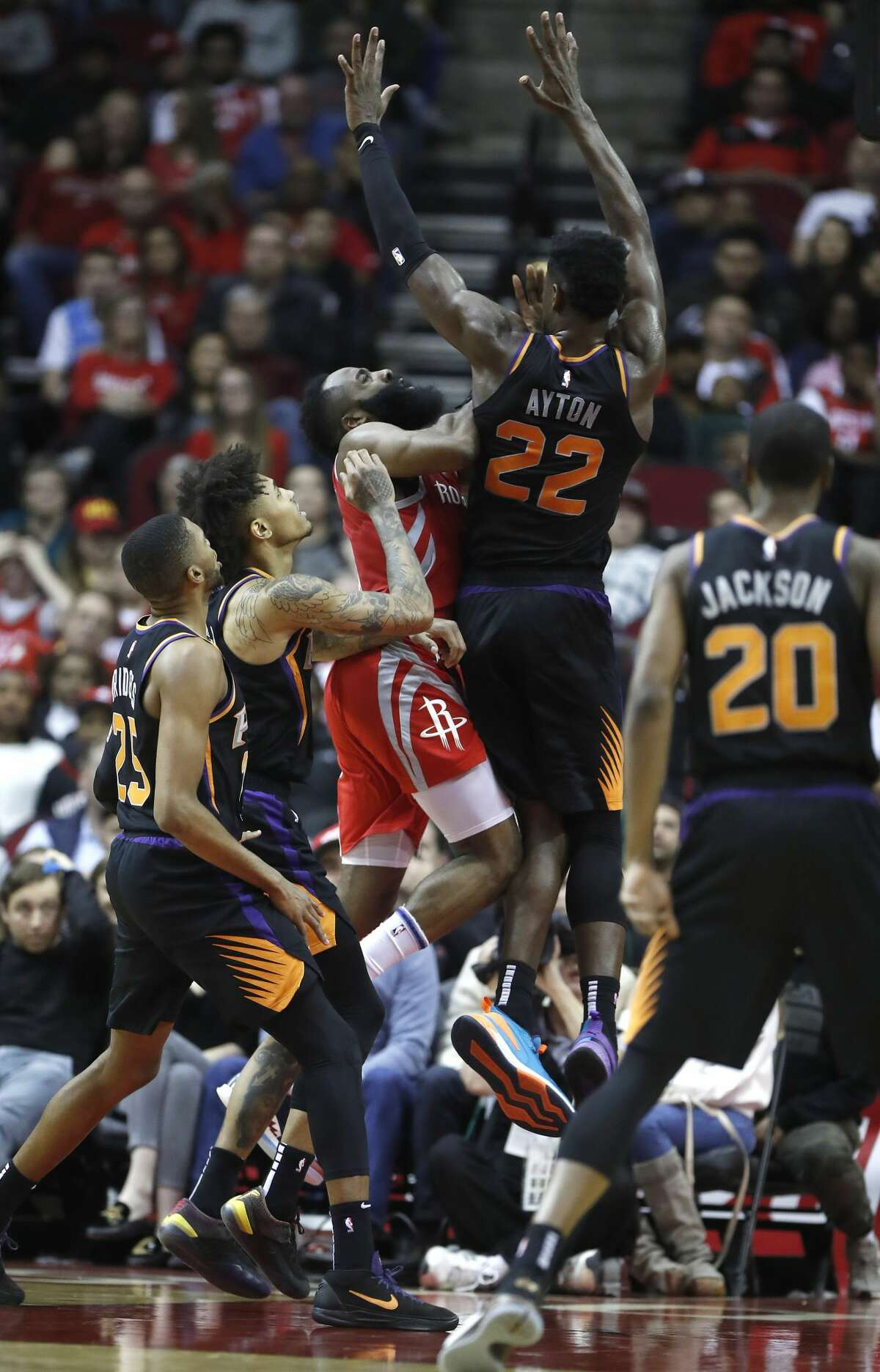 Houston Rockets guard James Harden (13) crashes into Phoenix Suns center Deandre Ayton (22) during the second half of an NBA game at Toyota Center, Friday, March 15, 2019, in Houston. Rockets won the game 108-102.