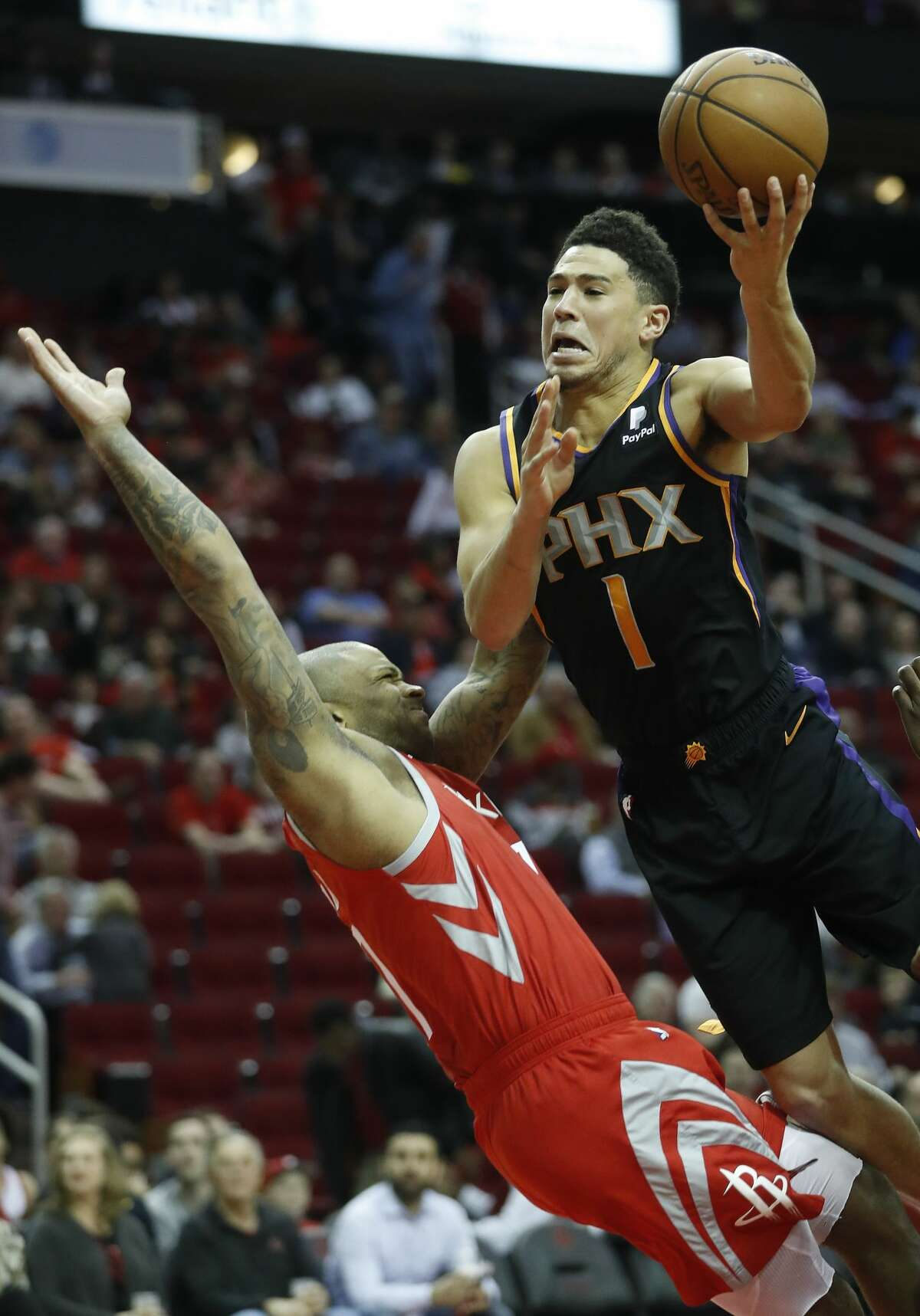Phoenix Suns guard Devin Booker (1) knocks down Houston Rockets forward PJ Tucker (17) on his way to the basket during the second half of an NBA game at Toyota Center, Friday, March 15, 2019, in Houston. Rockets won the game 108-102.