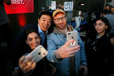 Presidential candidate Andrew Yang (center) takes photos with supporters Paola Perez (left) and Johnny Greavu at Yang�s campaign rally at SPARK Social SF on Friday, March 15, 2019, in San Francisco, Calif.