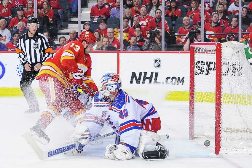 CALGARY, AB - MARCH 15: Johnny Gaudreau #13 of the Calgary Flames scores on Alexandar Georgiev #40 of the New York Rangers during an NHL game at Scotiabank Saddledome on March 15, 2019 in Calgary, Alberta, Canada. (Photo by Derek Leung/Getty Images)
