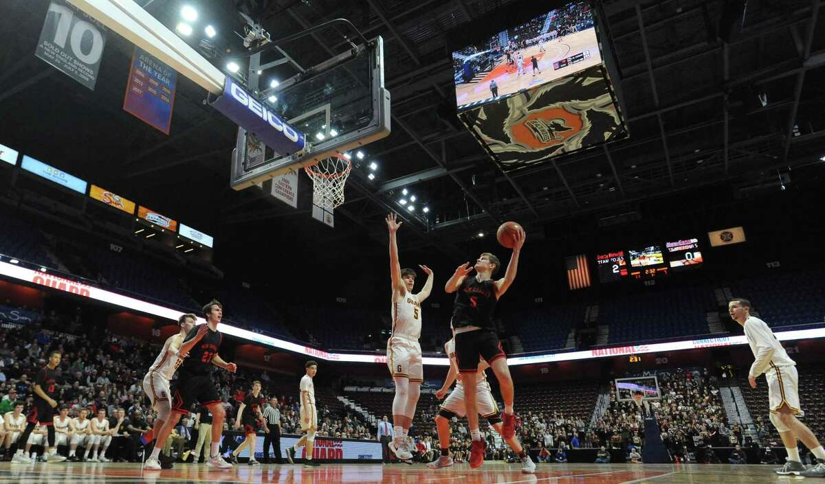 New Canaan's Alexander Gibbens (5) puts up a shot under pressure from Granby's Dylan Disbella during the first half of the CIAC 2019 State Boys Basketball Tournament Division IV finals at Mohegan Sun Arena in Uncasville, Conn. on Friday, March 16, 2019. New Canaan defeated Granby 55-39.