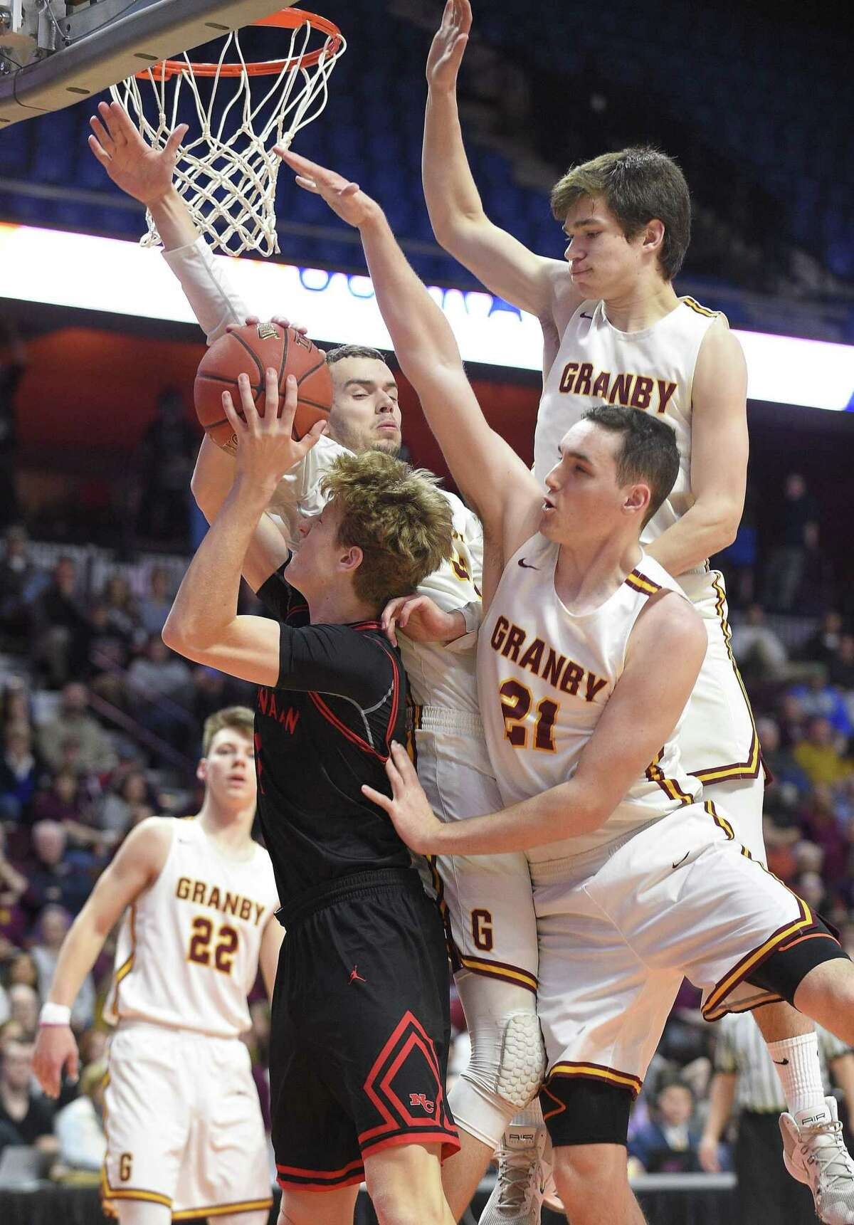 New Canaan's Matthew Brand (1) is fouled by Gramby players on his shot in the third quarter on Saturday.