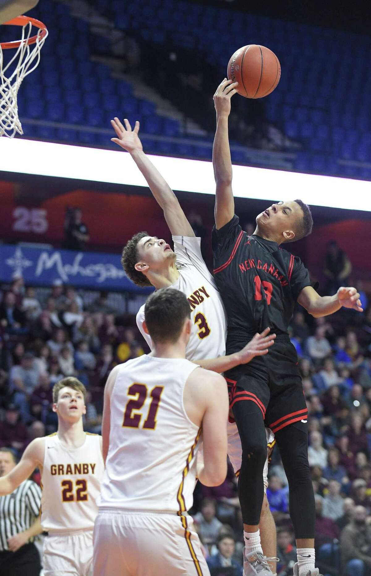 New Canaan's Luke Rwambuya (13) finger rolls a shot against Gramby's Elliyas Delaire (3) in the second half of the CIAC Division IV finals at Mohegan Sun Arena in Uncasville on Saturday. New Canaan defeated Gramby 55-39.