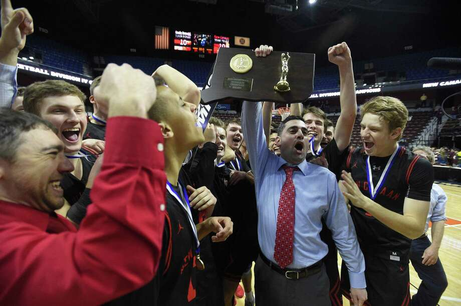 New Canaan coach Danny Melzer holds up the championship plaque with his team after defeating Granby on Saturday. Photo: Matthew Brown / Hearst Connecticut Media / Stamford Advocate