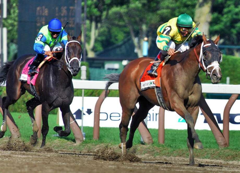 John Valasquez aboard Devil May Care, right, pulls away from Jose Lezcano and Acting Happy to win the Coaching Club American Oaks Grade I race at Saratoga Race Course. (John Carl D'Annibale / Times Union) Photo: John Carl D'Annibale / 00009594A
