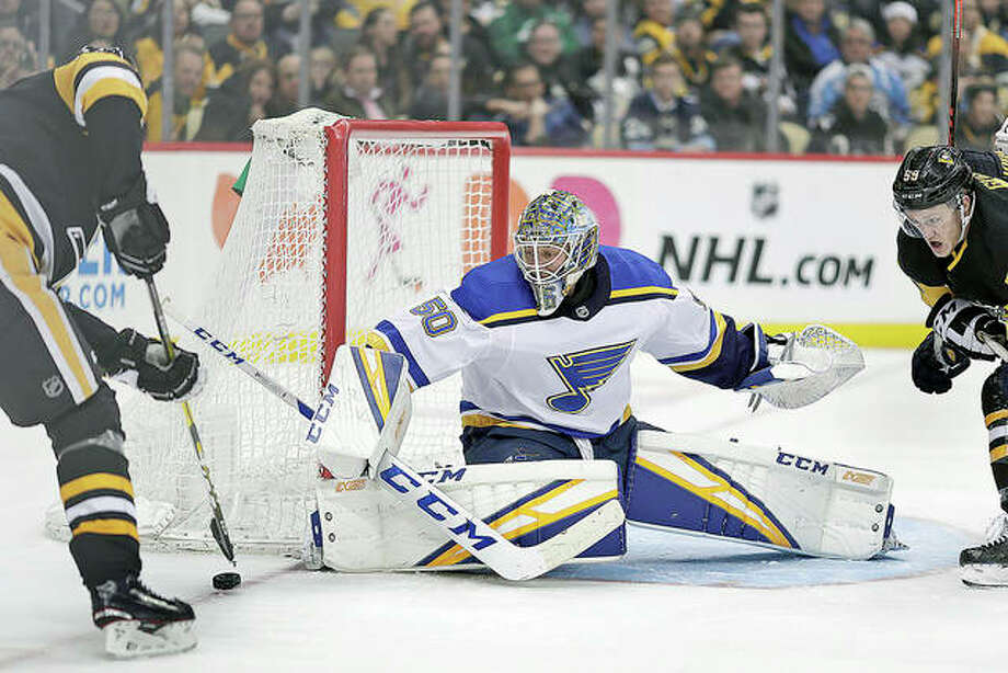Blues goaltender Jordan Binnington (50) blocks a shot by Penguin Evgeni Malkin, left, in the second period Saturday's game in Pittsburgh. Photo: AP Photo