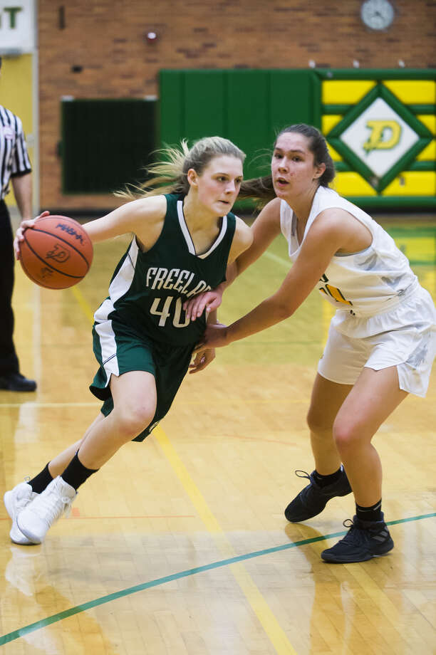 Freeland's Kadyn Blanchard drives by Dow High's Abby Rey during a game earlier this season. Photo: Daily News File Photo