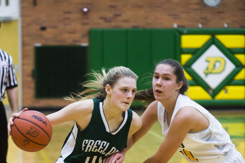 Freeland's Kadyn Blanchard drives by Dow High's Abby Rey during a game earlier this season.