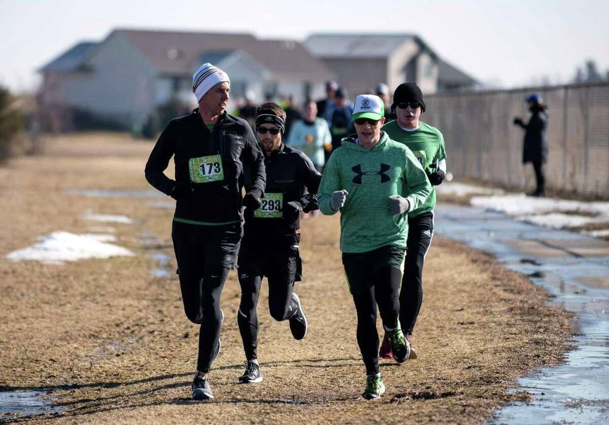 Beto O'Rourke, left, participates in the Lucky Run 5k race on Saturday in North Liberty, Iowa.