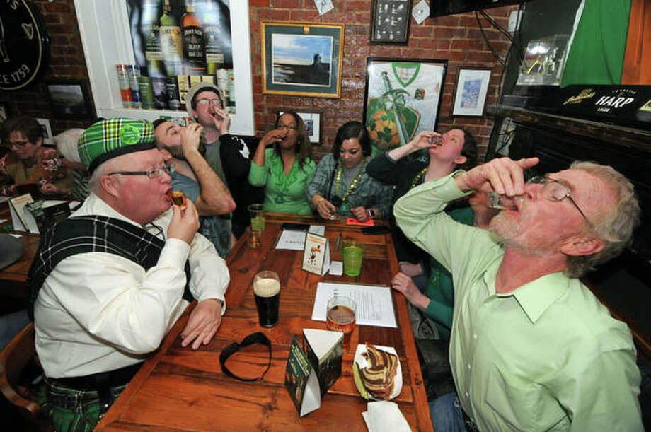 A group of friends in Morrison's Irish Pub downs a round of shots on Saturday. Photo: David Blanchette | For The Telegraph