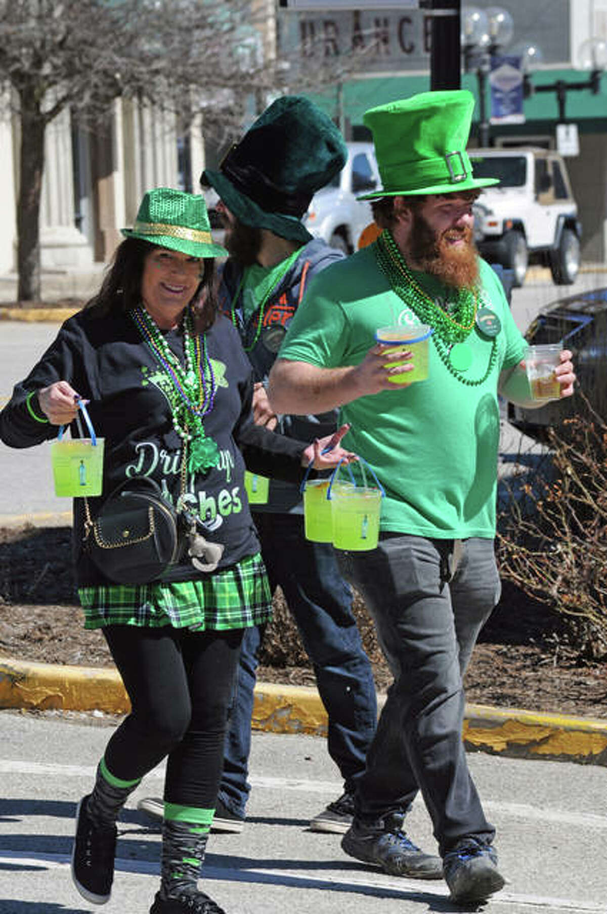 A pair of St. Patrick's Day revelers enjoy the mild weather on Saturday in downtown Alton.