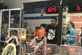 Members of the Crosby High School Robotics team, Alloy Obsession, control their robot during competition on March 15 at Channelview High School