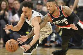 Derrick White, left, of the San Antonio Spurs and Damian Lillard of the Portland Trail Blazers fight for a loose ball during first-quarter NBA action in the AT&T Center on Saturday, March 16, 2019.