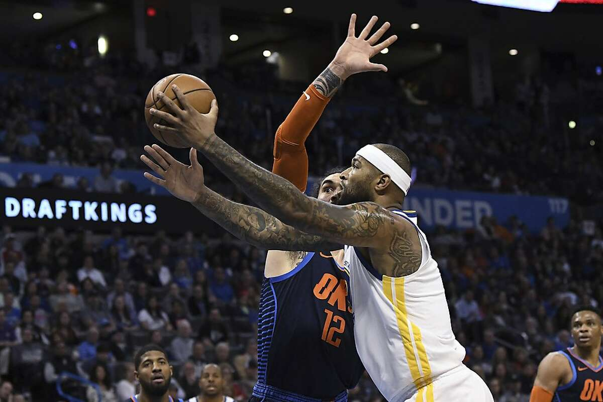 Golden State Warriors center DeMarcus Cousins (0) scores in front of Oklahoma City Thunder center Steven Adams (12) during the first half of an NBA basketball game Saturday, March 16, 2019, in Oklahoma City. (AP Photo/June Frantz Hunt)