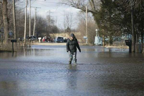 Allyson Hartman walks down flooded Louis Lane from her home on Friday, March 15, 2019, in Freeport, Ill. Rising waters along the Pecatonica and Rock rivers have flooded homes in northern Illinois. (Scott P Yates/Rockford Register Star via AP)