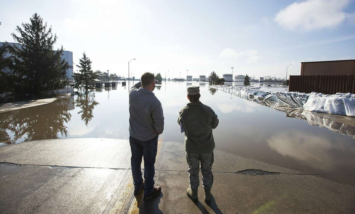 Luke Thomas and Air Force Tech Sgt. Vanessa Vidaurre look at a flooded portion of Offutt Air Force Base Sunday, March 17, 2015, in Bellevue, Neb. Hundreds of people were evacuated from their homes in Nebraska and Iowa as levees succumbed to the rush of water. Flooding has also been reported in Illinois, Minnesota, South Dakota and Wisconsin. (Z Long/Omaha World-Herald via AP)