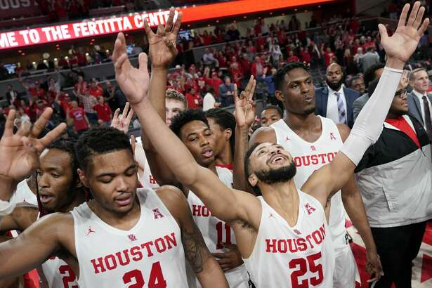 CAPTION ADDITION ADDS REGULAR-SEASON--Houston's Galen Robinson Jr. (25) raises his hands as he celebrates with teammates, including Breaon Brady (24) after an NCAA college basketball game against SMU Thursday, March 7, 2019, in Houston. Houston won 90-79 to clinch a share of the American Athletic Conference regular-season hampionship. (AP Photo/David J. Phillip)