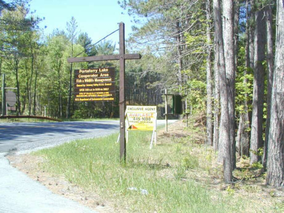 A for sale sign sits behind the entrance sign to Camp Portaferry near Pitcairn in the Adirondacks, a 465-acre Boy Scout camp that is up for sale.