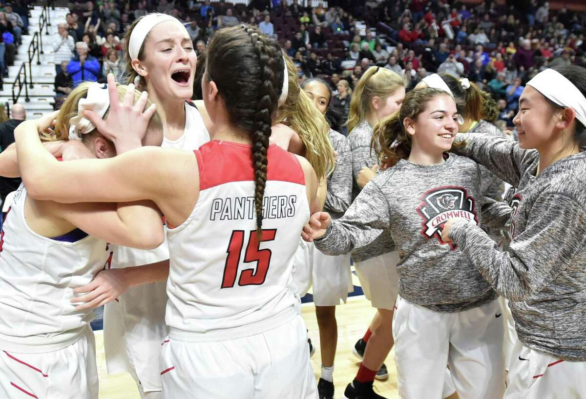 Members of the Cromwell girls basketball team celebrate their win over Sheehan in the Class M championship game on Sunday.