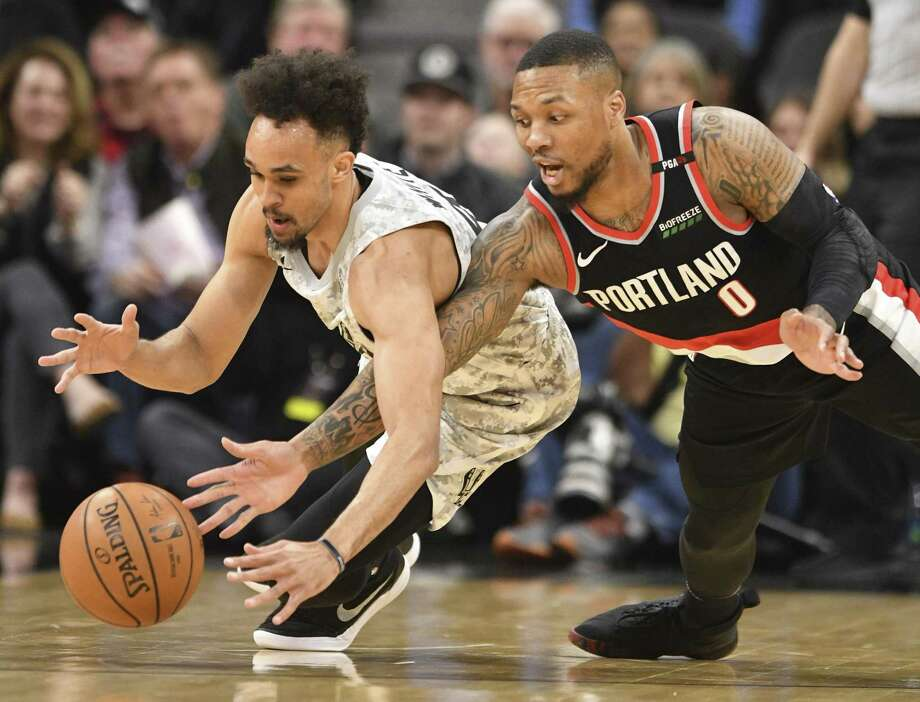 Derrick White, left, of the San Antonio Spurs and Damian Lillard of the Portland Trail Blazers fight for a loose ball during first-quarter NBA action in the AT&T Center on Saturday, March 16, 2019. Photo: Billy Calzada, Staff / Staff Photographer / San Antonio Express-News