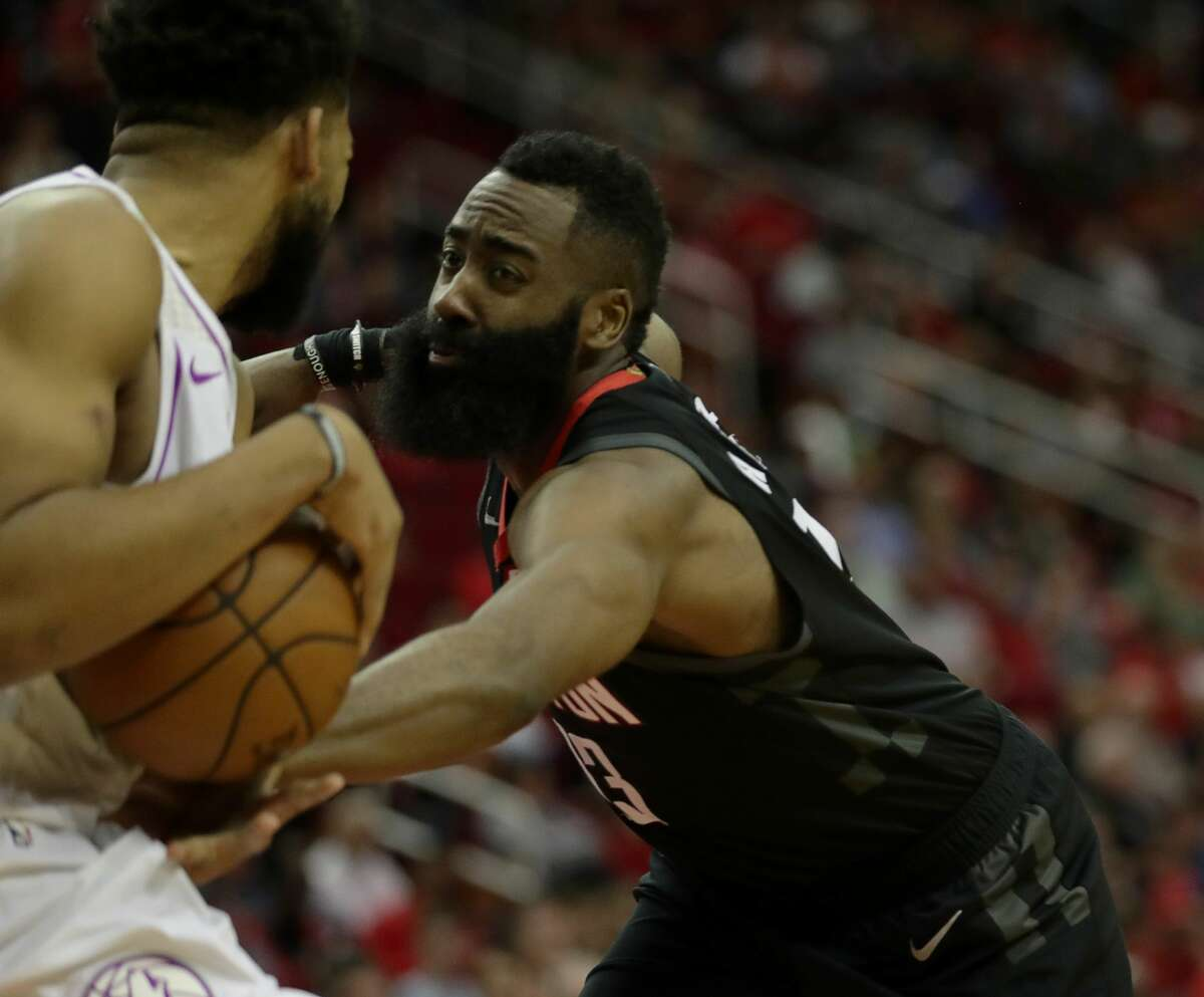 Houston Rockets guard James Harden (13) goes after the ball in the hands of Minnesota Timberwolves center Karl-Anthony Towns (32) during the fourth quarter of an NBA basketball game at the Toyota Center on Sunday, March 17, 2019, in Houston.
