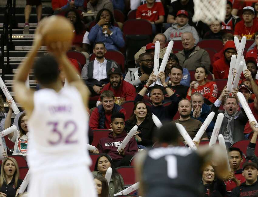 Audience members try to distract Minnesota Timberwolves center Karl-Anthony Towns (32) while he shoots a free throw during the first quarter of an NBA basketball game at the Toyota Center on Sunday, March 17, 2019, in Houston.